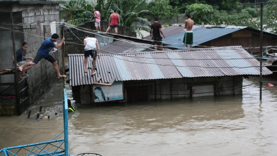 Filipinos move around roofs as floodwaters rise in suburban Quezon City, north of Manila, Philippines, on Tuesday Aug. 7, 2012. (AP / Mike Alquinto)