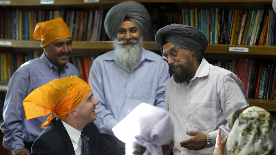 Wisconsin Gov. Scott Walker, lower left, is welcomed by members of the Sikh community as he prepares to worship with them at the Sikh Religious Society of Wisconsin, Monday, Aug. 6, 2012, in Brookfield, Wis. (AP / M. Spencer Green)