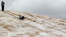A man slides down a hill after a rare snowfall in Johannesburg, South Africa, on Aug. 7, 2012.