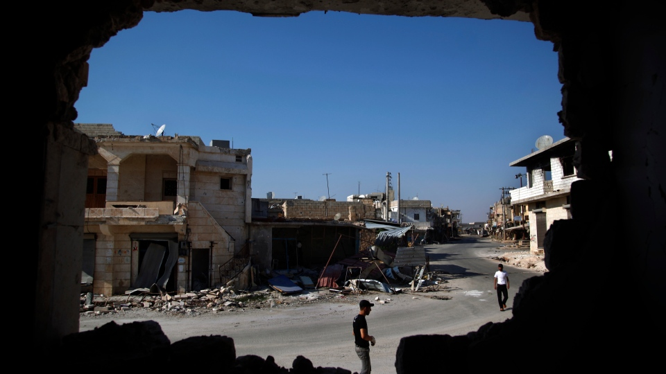 Syrians are seen through a destroyed wall as they walk on a street in town of Atareb outskirts of Aleppo, Syria, Sunday, Aug. 5, 2012. (AP / Khalil Hamra)