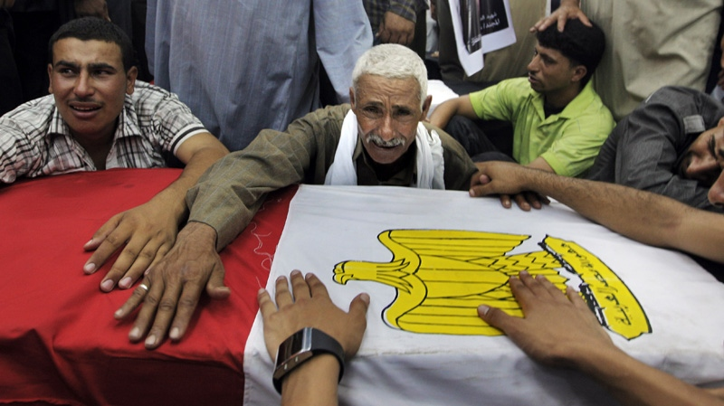 Relatives of an Egyptian soldier mourn during the funeral of one of 16 soldiers killed in an attack over the weekend by suspected militants in Sinai in Cairo, Egypt Tuesday Aug. 7, 2012. (AP Photo/Amr Nabil)