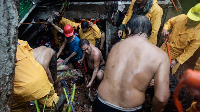 Filipino volunteers dig for survivors where four homes collapsed in a landslide in Quezon City, Philippines, Tuesday, Aug. 7, 2012. (AP / John Javellana)