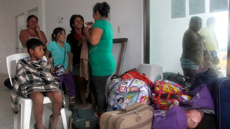 Residents arrive at a shelter in Mahahual, Mexico as Ernesto approaches, Tuesday, Aug. 7, 2012. (AP / Israel Leal)