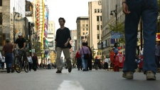 Pedestrians walk down the middle of Montreal's Ste-Catherine street Monday, Sept. 22, 2003, during its first-ever International Car-free Day, joining 954 cities around the world. (CP PHOTO/Paul Chaisson)