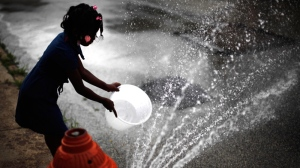 Jazia Pratt, 8, fills a bucket with water from a fire hydrant in the afternoon summer heat in Philadelphia, Wednesday, July 18, 2012. (AP / Matt Rourke)