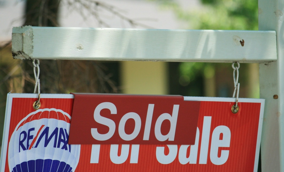 "A house ""sold"" sign is shown in Oakville, Ont., Monday, July 23, 2012. (Richard Buchan / THE CANADIAN PRESS)"