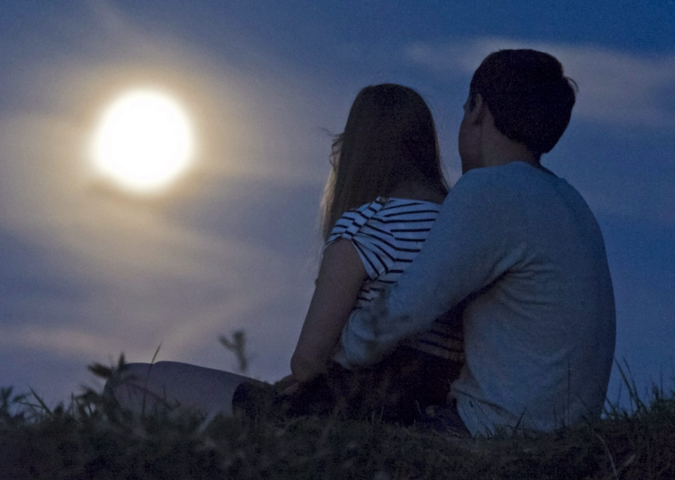 A man and a woman in front of the waning full moon in Erfurt, central Germany, Thursday, Aug. 2, 2012. (AP / Jens Meyer)