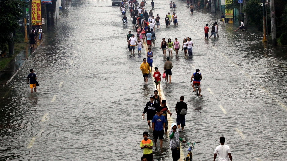 People walk on a flooded street Thursday, Aug. 9, 2012 in suburban Pasig City, east of Manila, Philippines. (AP / Pat Roque)