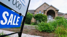 """A """"For Sale,"""" sign is displayed outside a home in Springfield, Ill., July 15, 2010. (AP / Seth Perlman)"""
