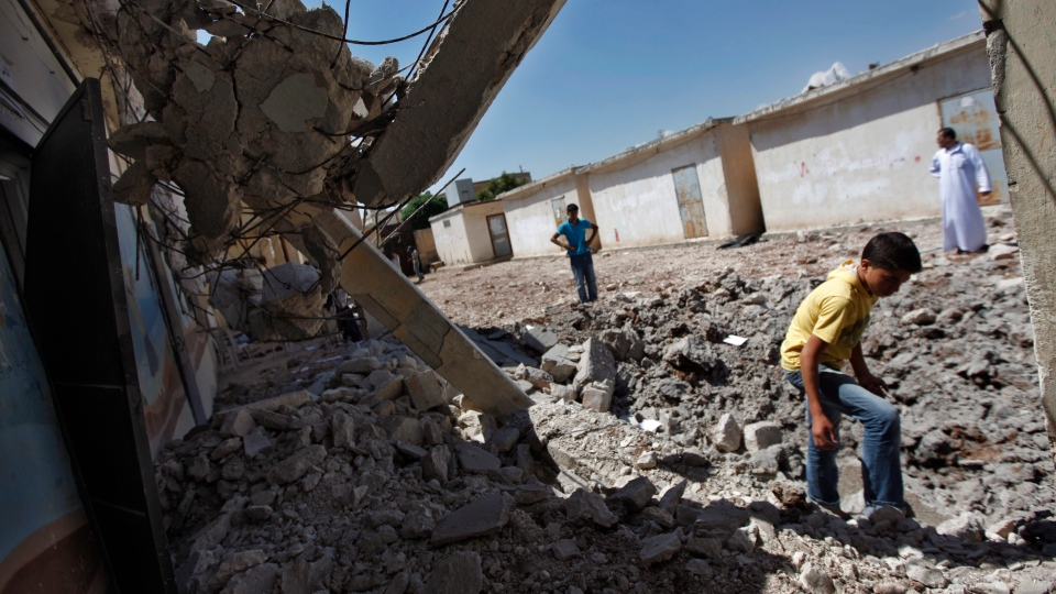 Syrians check the damage of a destroyed school after it was hit by an air strike killing six Syrians in town of Tal Rifat on the outskirts of Aleppo city, Syria, Wednesday, Aug. 8, 2012. (AP / Khalil Hamra)