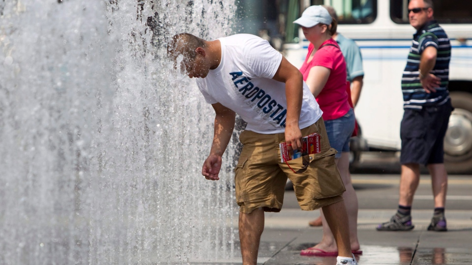 A man sticks his head in a fountain as a heat wave hits Toronto Thursday, July 21, 2011. (Darren Calabrese / THE CANADIAN PRESS)