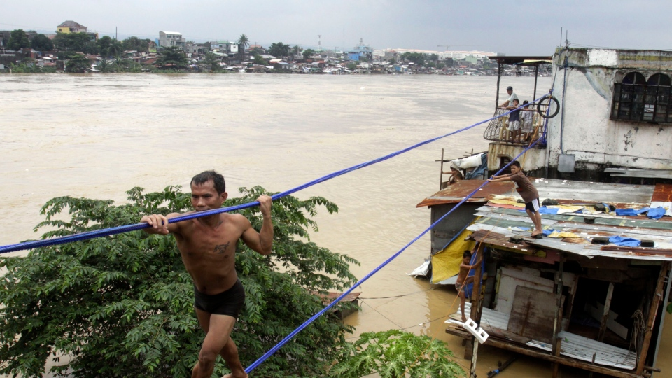 A man uses ropes to move to safer grounds as a river overflows in suburban Cainta City, east of Manila, Philippines, Thursday, Aug. 9, 2012. (AP / Pat Roque)