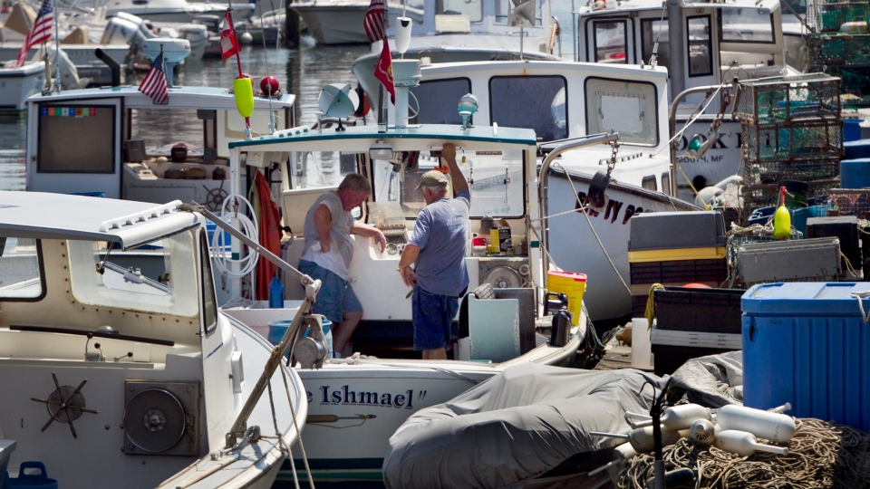 Lobstermen take a break while doing maintenance work, Thursday, August 9, 2012, in Portland, Maine. (AP/Robert F. Bukaty)