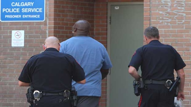 Fred Childress is led into the Arrest Processing Unit in Calgary, August 8, 2012. (Photo Courtesy: C