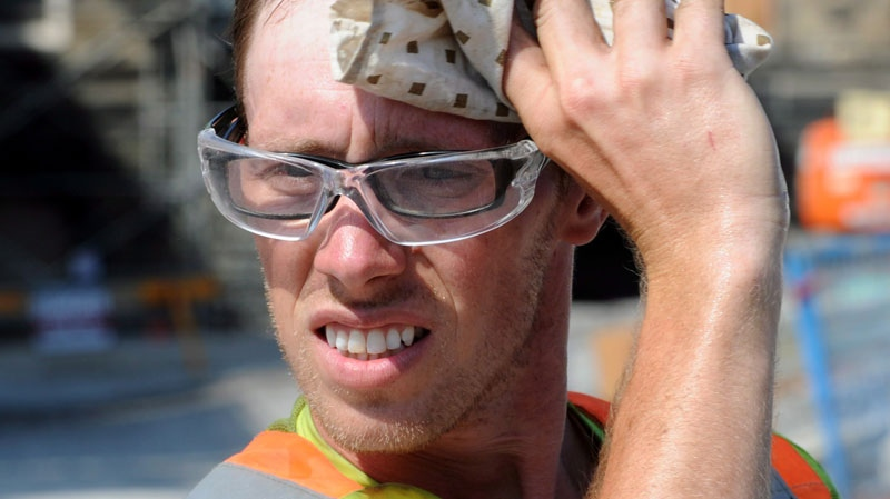 A construction worker wipes sweat from his brow as he works on Parliament Hill in Ottawa on Thursday, June 21, 2012. (Sean Kilpatrick / THE CANADIAN PRESS)