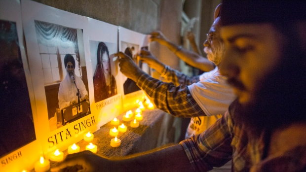Members of the Sikh community place votive candles beside photographs of the victims of the Wisconsin Sikh Temple shooting during a vigil Wednesday, Aug. 8, 2012 in New York's Union Square. (AP / John Minchillo)