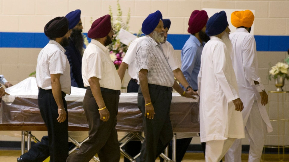 Sikh temple members bring in a casket for the funeral and memorial service for the six victims of the Sikh Temple of Wisconsin mass shooting in Oak Creek, Wis., Friday, Aug 10, 2012. (AP / Jeffrey Phelps)