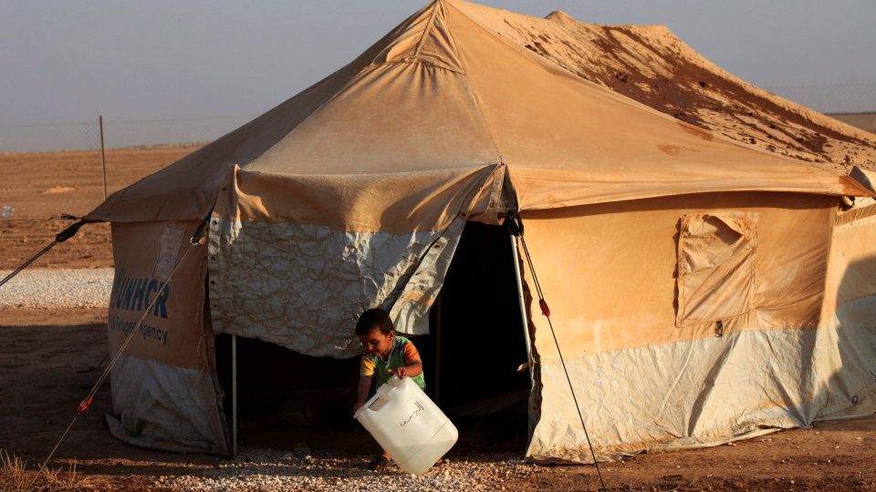 A Syrian refugee boy washes his hands outside his family's tent in the Zaatari Syrian Refugee camp, in Mafraq, Jordan, Thursday, Aug. 2, 2012. (AP / Mohammad Hannon)