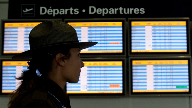 An airport security guard walks past a departures panel at the Montreal Trudeau airport, Tuesday, Ja
