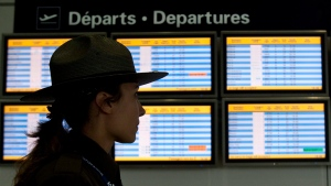 An airport security guard walks past a departures panel at the Montreal Trudeau airport, Tuesday, January 5, 2010 in Montreal. (Paul Chiasson / THE CANADIAN PRESS)