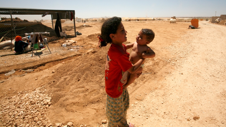 Syrian refugees walk through Zaatari refugee camp in Mafraq, Jordan, Friday, Aug. 10, 2012. (AP / Mohammad Hannon)