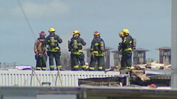 Fire crews stand on the roof of the Maple Leaf Foods plant in St. Boniface to battle a fire.