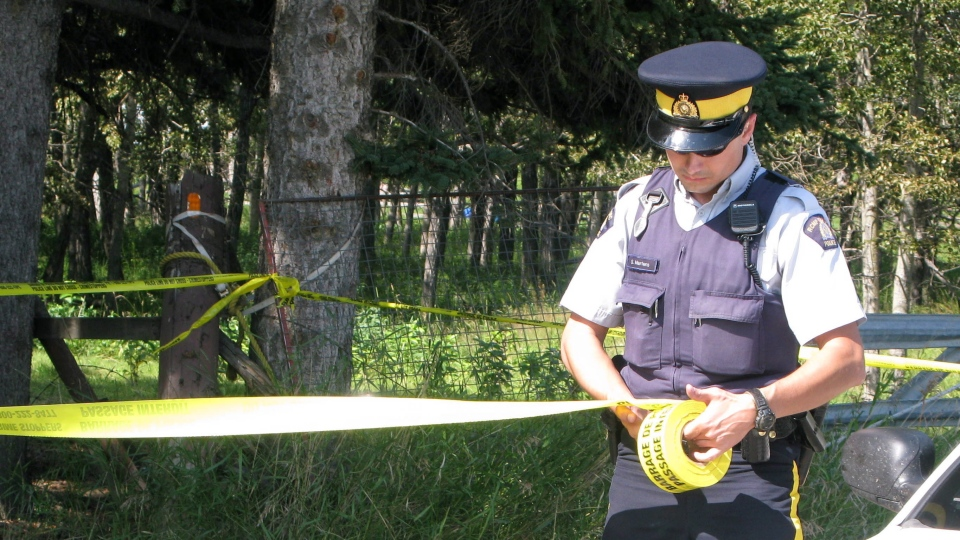 An RCMP officer puts up police tape near a rural residence south of Calgary, Friday, Aug. 10, 2012. (Bill Graveland / THE CANADIAN PRESS)