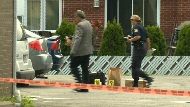 Police are shown at the scene where a 42-year-old man was fatally shot in Montreal on Saturday, Aug. 11, 2012.