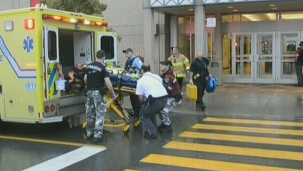 Paramedics are shown putting a shooting victim into an ambulance outside the Galeries d'Anjou shopping centre in Montreal on Friday, Aug. 10, 2012.
