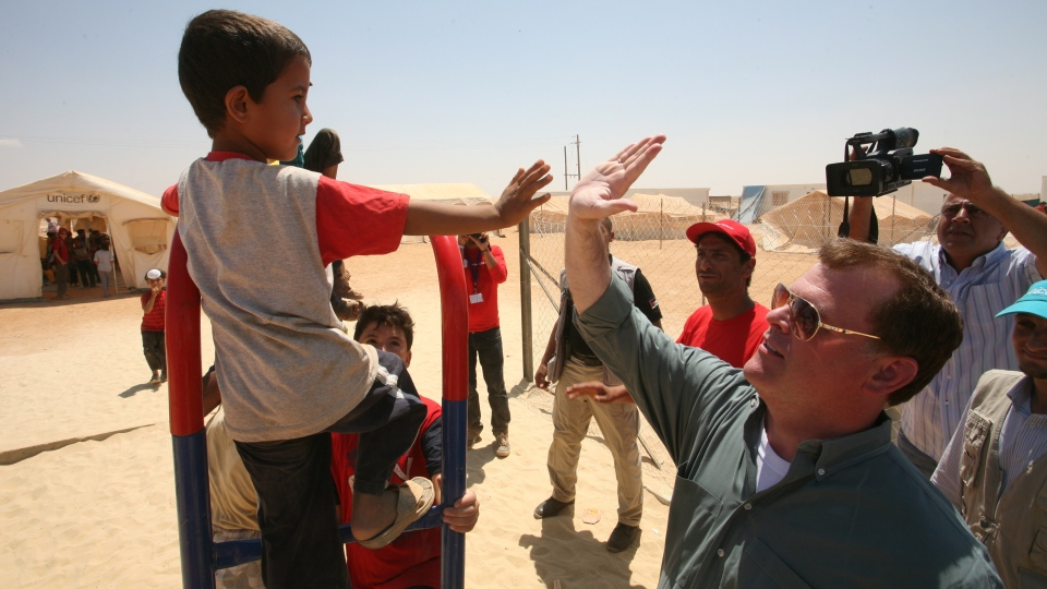 Foreign Affairs Minister John Baird greets a Syrian refugee boy at Zaatari refugee camp, in Mafraq, Jordan, Saturday, Aug. 11, 2012. (AP / Mohammad Hannon)