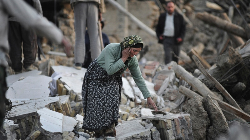 A female victim of Saturday's earthquake makes her way on the ruins of buildings in a village near the city of Varzaqan in northwestern Iran on Sunday, Aug. 12, 2012.  (AP / Mehr News Agency, Mahsa Jamali)