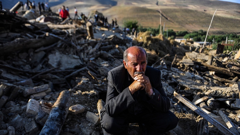 A victim of Saturday's earthquake sits on the ruins of buildings at the village of Bajebaj near the city of Varzaqan in northwestern Iran on Sunday, Aug. 12, 2012. (AP / ISNA, Ruhollah Vahdati)