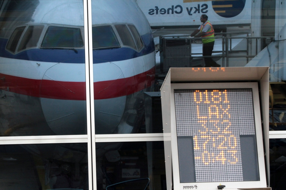 A countdown to departure clock is framed by a reflection of an American Airlines fleet clerk servicing an airplane at JFK International airport in New York on Aug. 1 2012 photo, a. (AP / Mary Altaffer)
