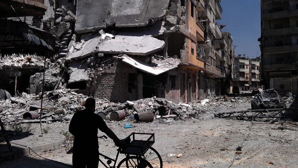 In this citizen journalism image provided by Shaam News Network SNN, taken on Saturday, Aug. 11, 2012, a man looks at destroyed buildings from Syrian forces shelling in Khaldiyeh, Homs, Syria. (AP / Shaam News Network, SNN)
