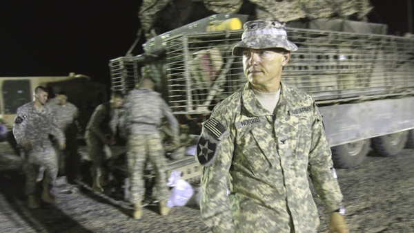 U.S. Army Col. John Norris, commander of the 4th Stryker Brigade Combat Team, 2nd Infantry Division, waits for the last Stryker armored vehicle carrying his soldiers to arrive after crossing into Kuwait from Iraq, Thursday, Aug. 19, 2010. (AP / Maya Alleruzzo)
