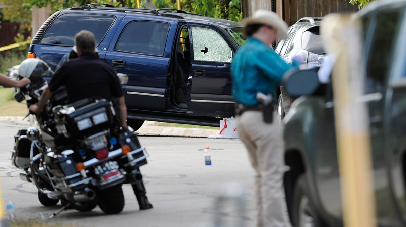 Law enforcement officials investigate an area where police say a gunman was being served an eviction notice when he opened fire from inside a home near Texas A&M and killed a law enforcement officer in College Station, Texas on Monday, Aug. 13, 2012. (AP / Pat Sullivan)