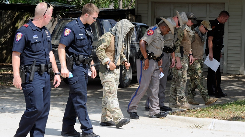 Law enforcement officials conduct a grid search of an area where police say a gunman was being served an eviction notice when he opened fire from inside a home near Texas A&M and killed a law enforcement officer in College Station, Texas on Monday, Aug. 13, 2012. (AP / Pat Sullivan)