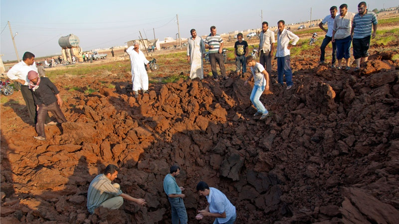 Syrian men inspect a hole allegedly made during an airstrike by government forces in the town of Marea, Syria, Monday, Aug. 13, 2012. (AP / Khalil Hamra)