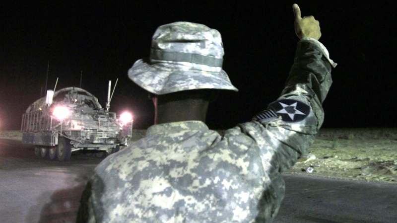 U.S. Army Spc. Luisito Brooks gives a thumbs-up to the last Stryker armoured vehicle to leave Iraq  as it crosses the border into Kuwait at the Khabari border crossing, Thursday, Aug. 19, 2010. (AP / Maya Alleruzzo)