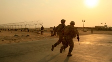 U.S. Army soldiers from 2nd Battalion, 23rd Infantry Regiment, 4th Brigade, 2nd Infantry Division race toward the border from Iraq into Kuwait on Wednesday, Aug. 18, 2010. (AP / Maya Alleruzzo)
