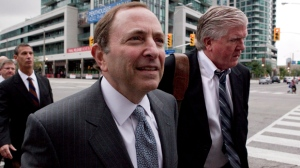NHL commissioner Gary Bettman, centre, and Toronto Maple Leafs general manager Brian Burke, right, arrive for collective bargaining talks in Toronto on Tuesday, Aug. 14, 2012. (The Canadian Press/Chris Young)