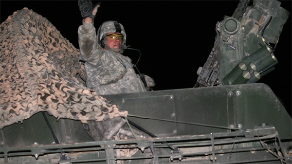 A soldier with the 4th Stryker Brigade Combat Team, 2nd Infantry Division, waves as he and his fellow Strykers roll across the border from Iraq into Kuwait in the early morning hours of Thursday, Aug. 19, 2010. (1st Sustainment Command (Theater) Public Affair / U.S. Army)
