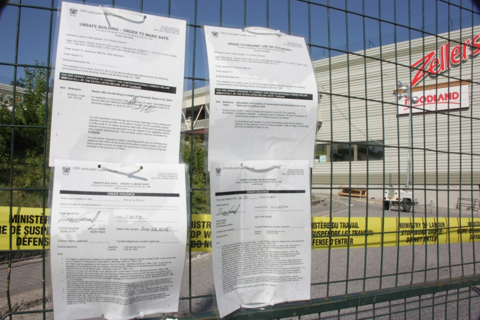 City orders sit affixed to emergency fencing around the Algo Centre Mall in Elliot Lake, Ont., on Tuesday, Aug. 14, 2012. (Colin Perkel / THE CANADIAN PRESS)