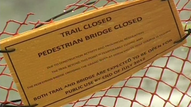 A sign indicates the pedestrian bridge on the Walter Bean Trail in Kitchener, Ont. is closed, Tuesday, Aug. 14, 2012.