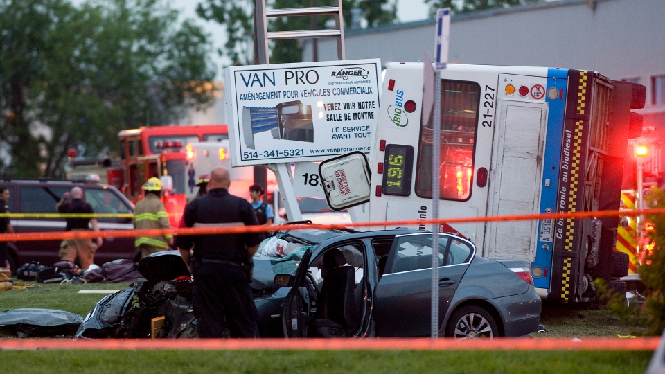 Police officers survey the scene where two people where killed in a collision between a bus and two cars in Montreal, Tuesday, August 14, 2012. (Graham Hughes / THE CANADIAN PRESS)