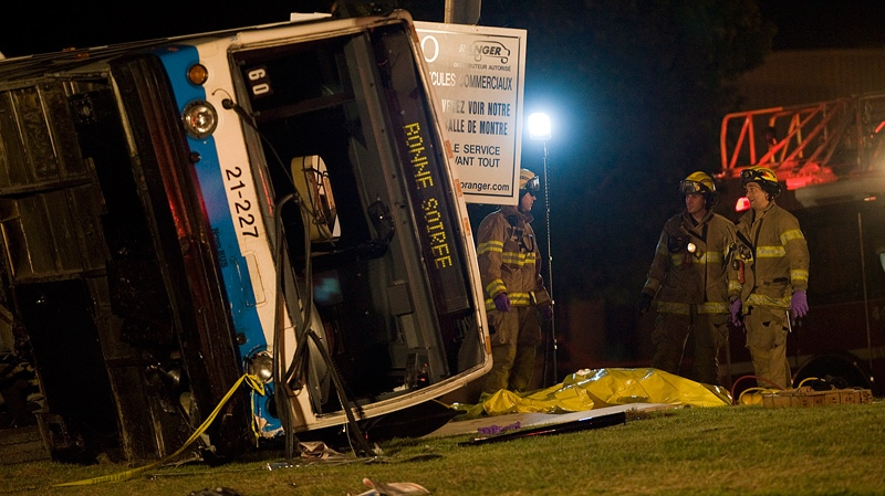 A body, covered in a yellow tarp, lies next to a bus at the scene where two people where killed in a collision between the bus and two cars in Montreal, Tuesday, August 14, 2012. (Graham Hughes / THE CANADIAN PRESS)