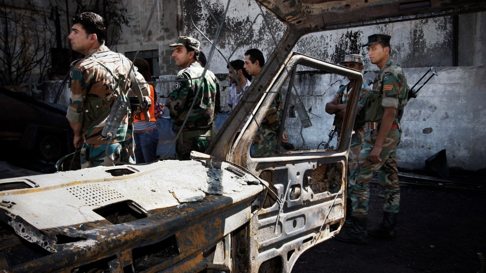Syrian soldiers investigate the scene after a bomb attached to a fuel truck exploded outside a Damascus hotel where U.N. observers are staying in Damascus, Syria, Wednesday, Aug. 15, 2012. (AP / Muzaffar Salman)