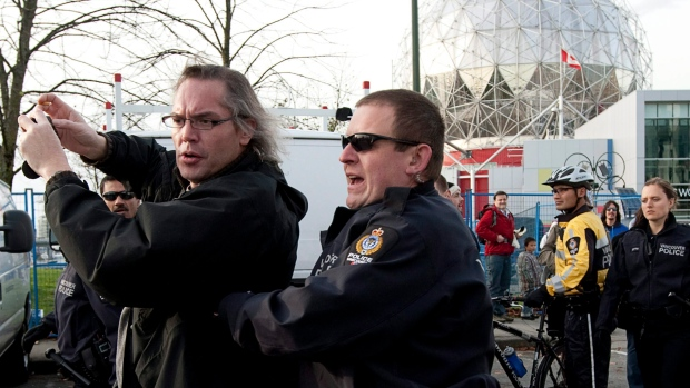 Vancouver Police Department moves a protester from in front of Prime Minister Stephen Harper