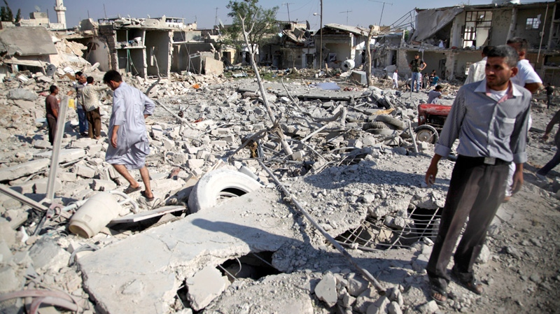 Syrians stand in rubble after an air strike destroyed at least ten houses in the town of Azaz on the outskirts of Aleppo, Syria on Wednesday, Aug. 15, 2012. (AP / Khalil Hamra)