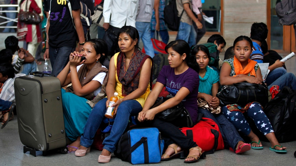 Women from India's northeastern states wait with their baggage to board trains home, at a railway station in Bangalore, India, Thursday, Aug.16, 2012. Thousands of Indians from the northeast are fleeing the southern city of Bangalore, spurred by rumors they would be attacked in retaliation for communal violence in their home state of Assam. (AP / Aijaz Rahi)